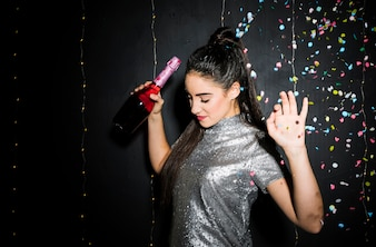 Woman with upping hands holding bottle of champagne near tossing confetti