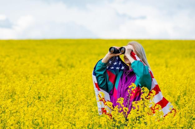 노란 유채 밭에서 미국 국기와 쌍안경을 가진 여자