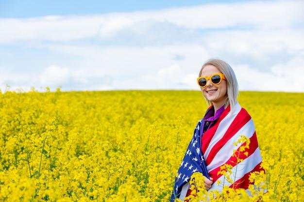 노란 유채 밭에 미국 국기를 가진 여자