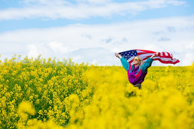 Woman with usa flag in yellow rapeseed field