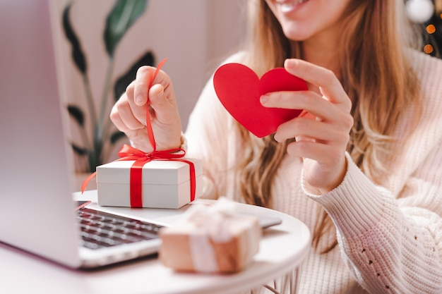Woman with valentine card and gift having a video chat on laptop