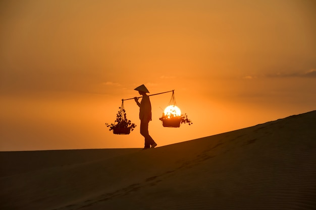 Woman with vietnam culture traditional dress on sandune during sunset ,traditional costume