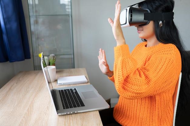 バーチャルリアリティメガネとコンピューターを持つ女性