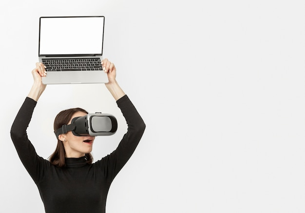 Woman with virtual reality headset holding laptop