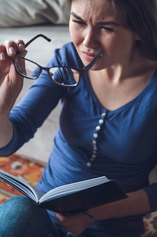 A woman with vision problems is reading a book with glasses