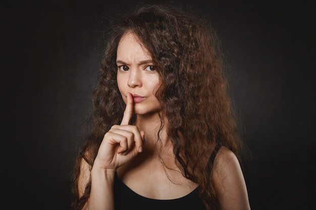 Woman with voluminous hair and clean skin frowning gesturing with fore finger at her lips, asking not to make nose while she's studying
