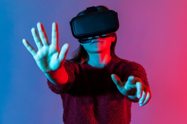 Woman with vr glasses headset standing outstretched hands choosing virtual menu, click button, playing game simulator, experiencing cyberspace. innovation, technology concept. neon light studio shot