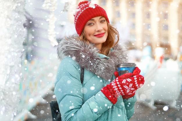 Женщина в теплой зимней куртке стоит на открытом воздухе