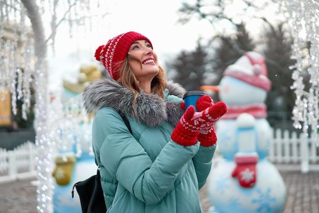 Женщина в теплом зимнем свитере, красной вязаной шапке и перчатках стоит на улице
