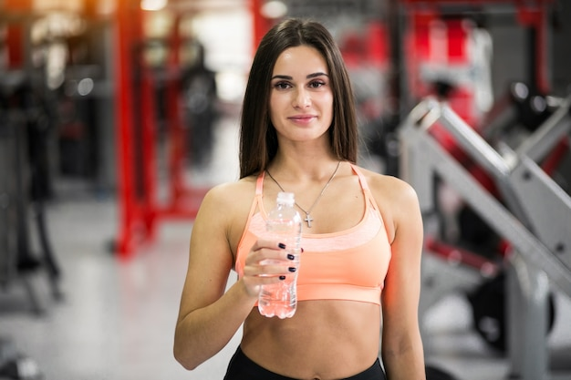 Woman with water at gym