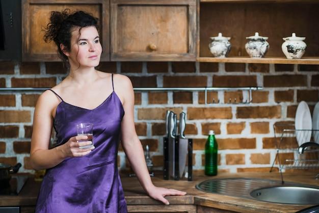 Женщина с водой на стильной кухне