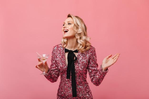 ウェーブのかかった髪の女性は笑ってピンクの壁にマティーニを楽しんでいます