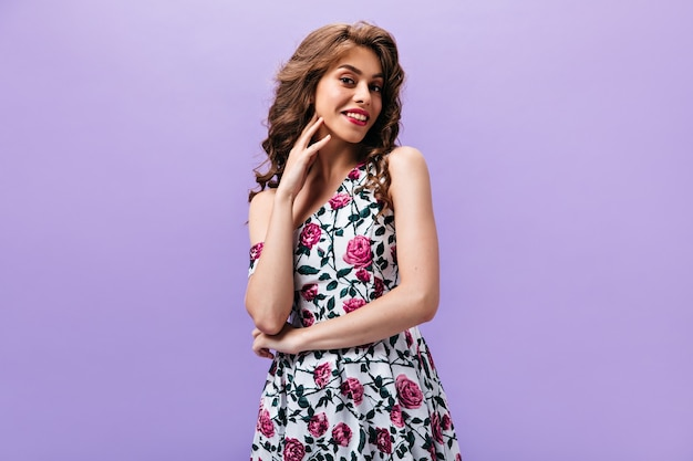 Woman with wavy hair looking into camera. wonderful girl with bright lips in summer stylish dress posing on isolated background.