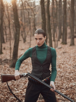 Woman with weapon in forest. hunter walking in forest.
