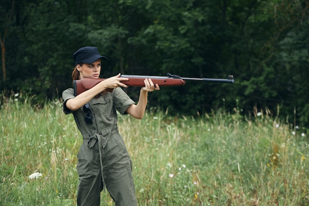 Woman with a weapon in hand, a hunting green jumpsuit is aiming fresh air close-up