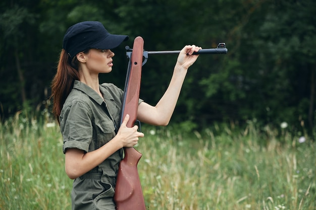 Woman with weapon in hands outdoors
