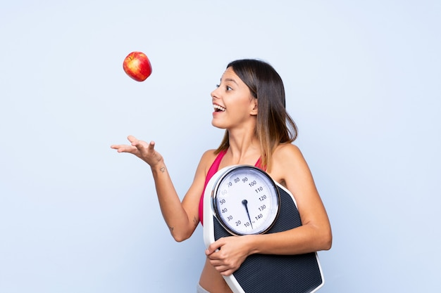 Woman with weighing machine over isolated blue with weighing machine and with an apple