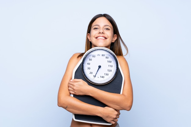 Woman with weighing machine over isolated blue with weighing machine