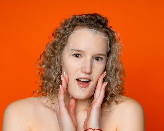 濡れた髪と裸の肩を持ち、透明な角質除去マスクをしている女性は、驚いて手で顔に触れ、レンズをのぞき込み、オレンジ色の壁に顔のケアをしている