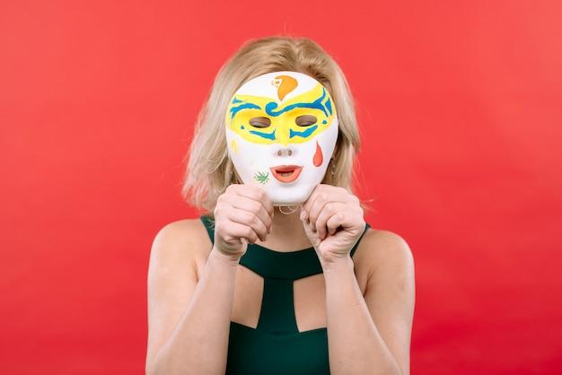 手、白いカーニバルマスクを持つ女性