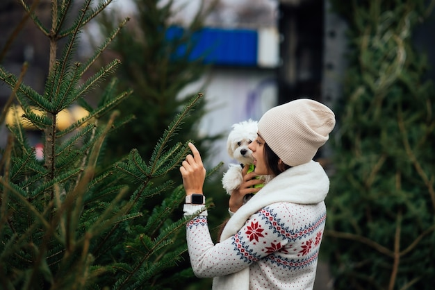 Woman with a white dog in her arms near a green christmas trees at the market