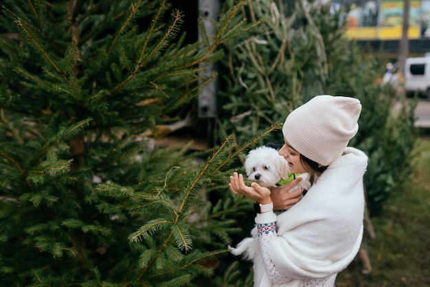 Donna con un cane bianco in braccio vicino a un albero di natale verde al mercato