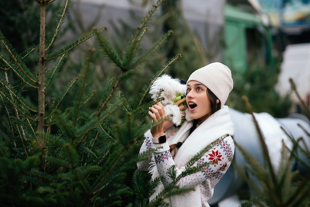 Woman with a white dog in her arms near a green christmas trees