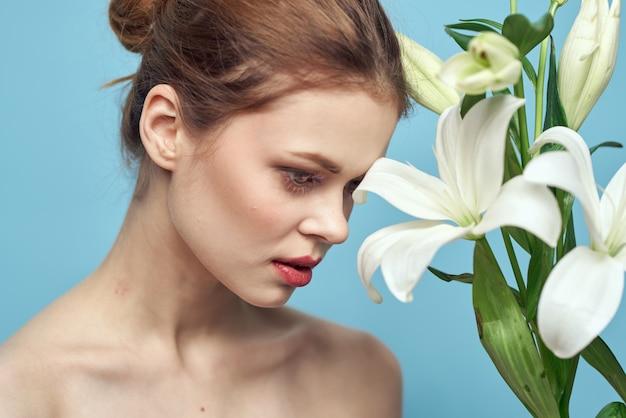 青い壁のトリミングされたビューに白い花を持つ女性