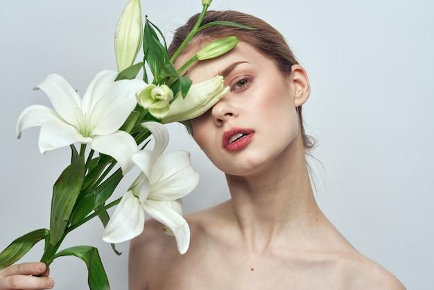 灰色の背景の肖像画のクローズアップメイクモードで白い花を持つ女性