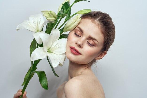 灰色の壁の肖像画のクローズアップメイクモードで白い花を持つ女性。