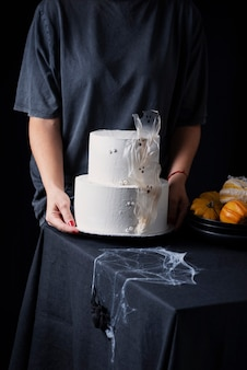 Woman with white frosting cake,  halloween decoration on the black table, selective focus image