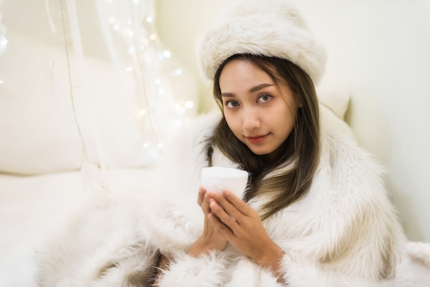 Woman with white fur hat and sweater drink coffee