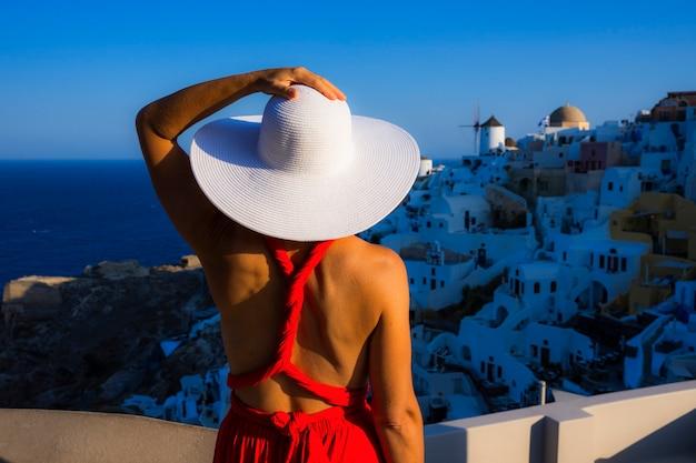 Женщина в белой шляпе в ия, санторини, греция