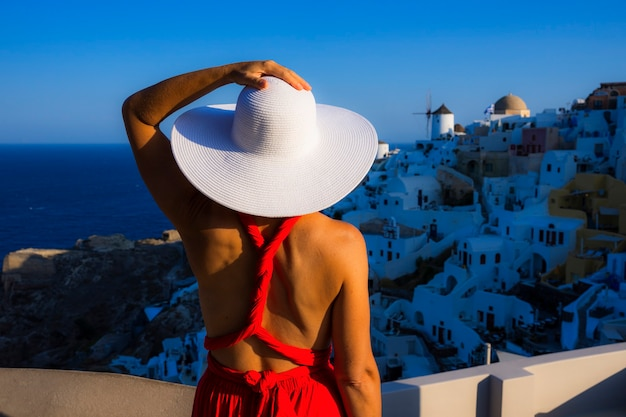 Woman with white hat in oia, santorini, greece