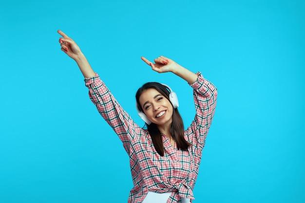 Женщина в белых наушниках слушает музыку и танцует с поднятыми руками