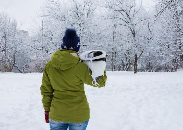 하얀 아이스 스케이트를 탄 여자가 눈 덮인 정원을 바라보고 있다