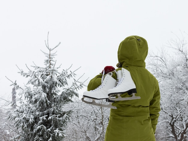 Woman with white ice skates looks at the snow-covered spruce