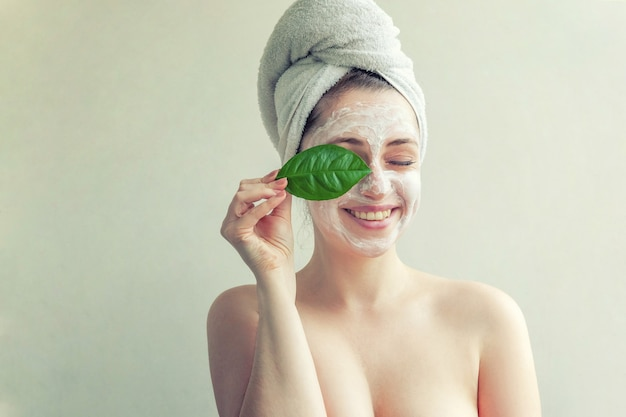 Женщина с белой питательной маской или кремом на лице и зеленым листом в руке, белый фон