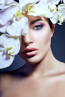 Woman with white orchid near face