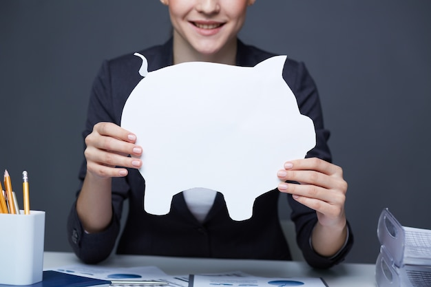 Woman with a white piggy bank