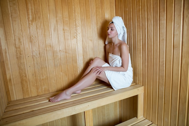 Woman with white robe sitting in a hot sauna