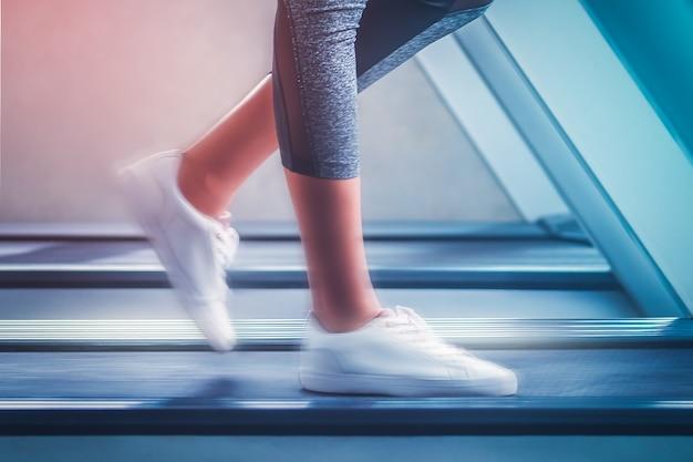 白い靴を履いた女性は、モーションブラー効果のあるトレッドミルを高速で歩いています