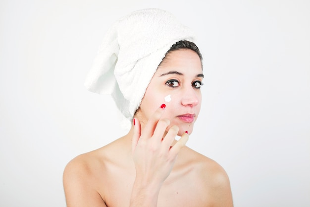 Woman with white towel wrapped around her head applying cream over the face