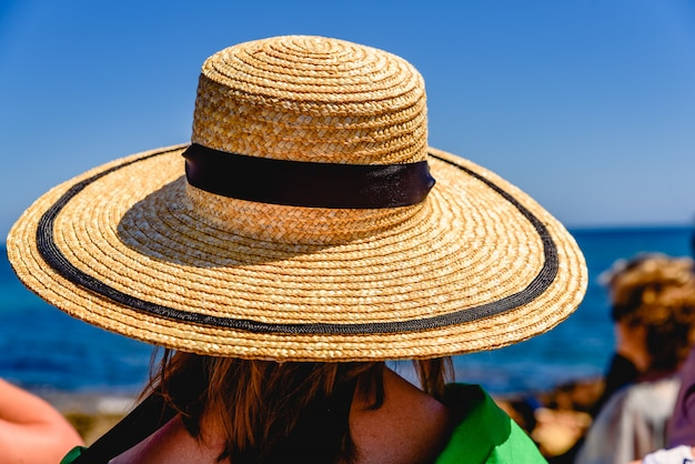 Woman with a wide straw hat to protect herself from the sun, elegantly dressed, during an outdoor event.