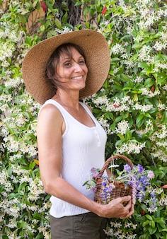 自然療法と植物学のためのバスケットに野生の花を持つ女性