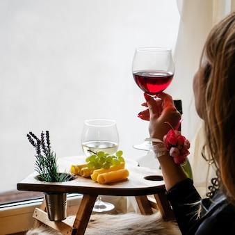 Женщина с бокалом вина, сидя у окна. день святого валентина