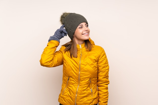 Woman with winter hat having doubts and with confuse face expression