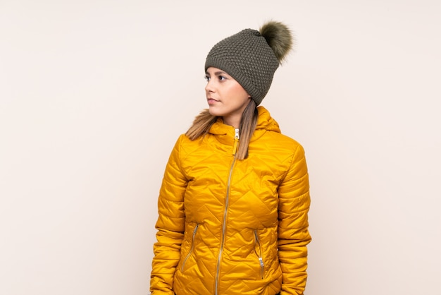 Woman with winter hat over isolated wall looking side