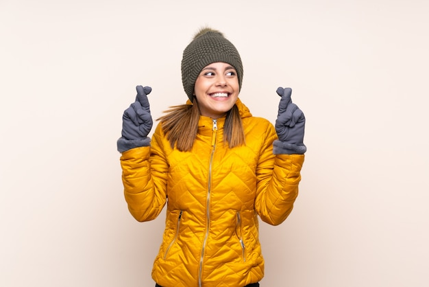 Woman with winter hat over wall with fingers crossing