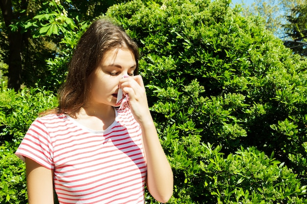 Woman with with allergy symptom blowing nose